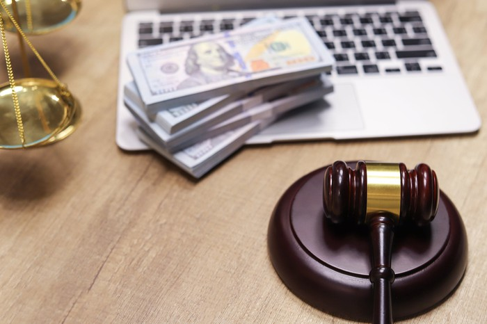A gavel near a laptop with piles of 100 dollar bills and a scale nearby.