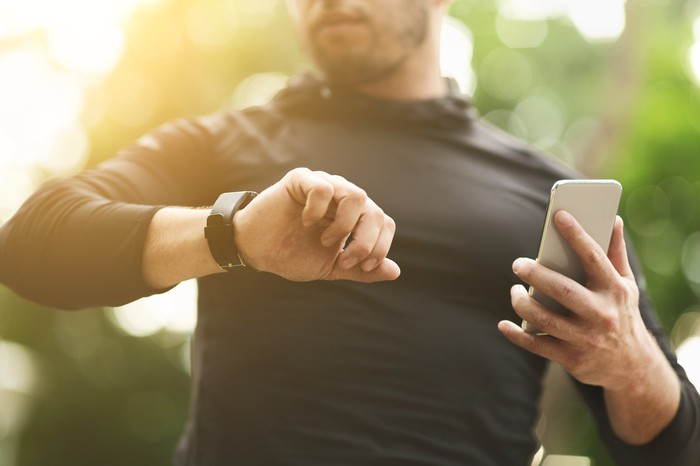 A man using a fitness tracker and smartphone.