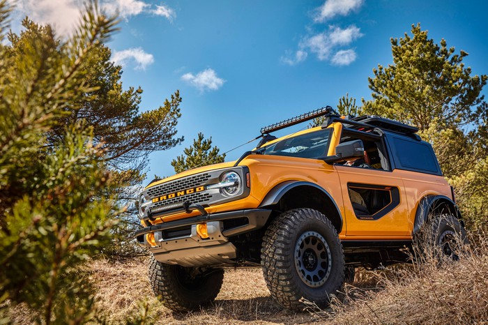 A yellow two-door 2021 Ford Bronco, an off-road SUV, shown on a hillside.