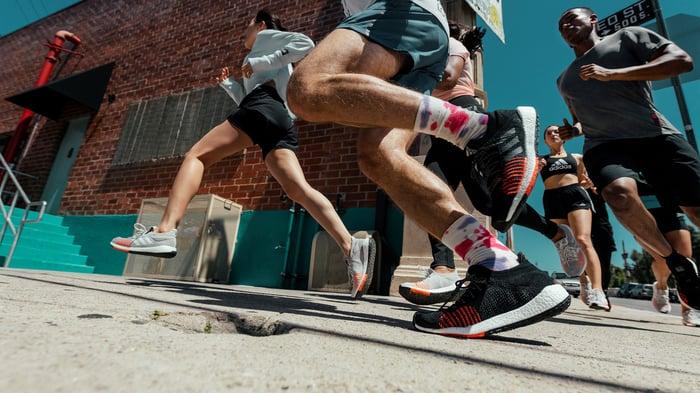 Men and women running on a sidewalk wearing Adidas running shoes.