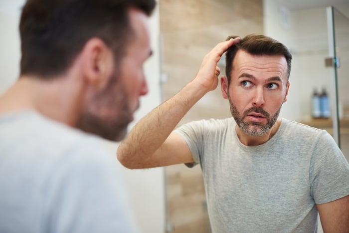 A man checks his hair in the mirror.