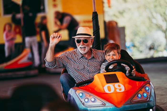 Older man in sunglasses and hat riding bumper car with young boy.
