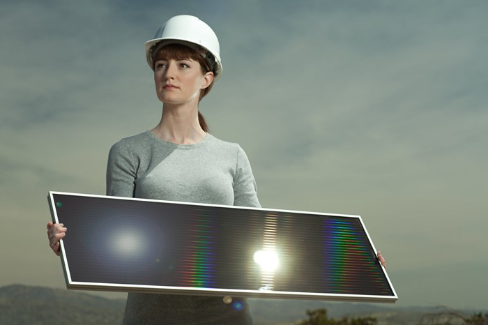 Woman in a hard hat holding a solar panel reflecting sunlight.
