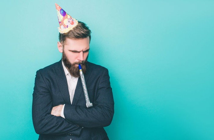 A man in a suit wearing a party hat and blowing a noisemaker