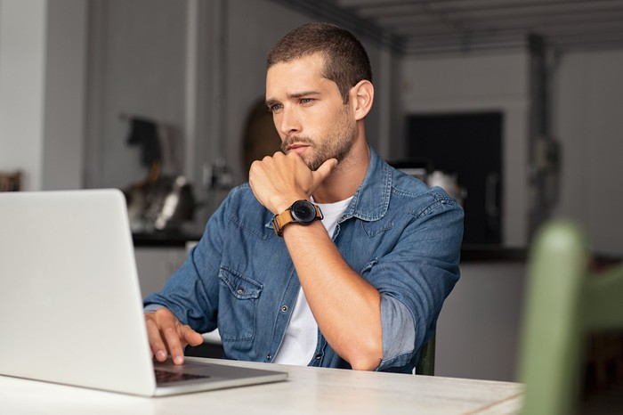 Man with a serious facial expression using a laptop.