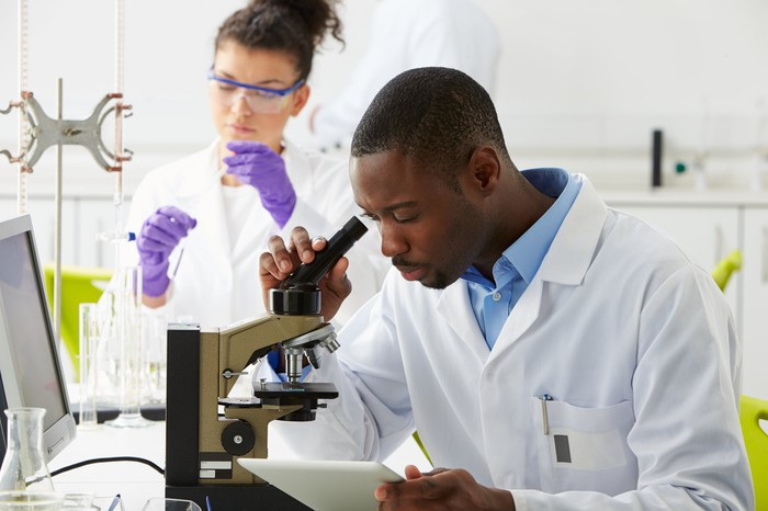 Two scientists working in a lab, with one looking through a microscope