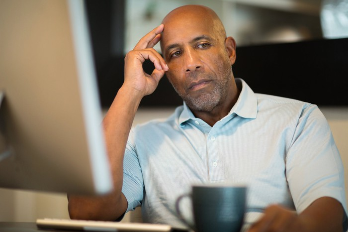 Older man sitting at desk with a serious look on his face.