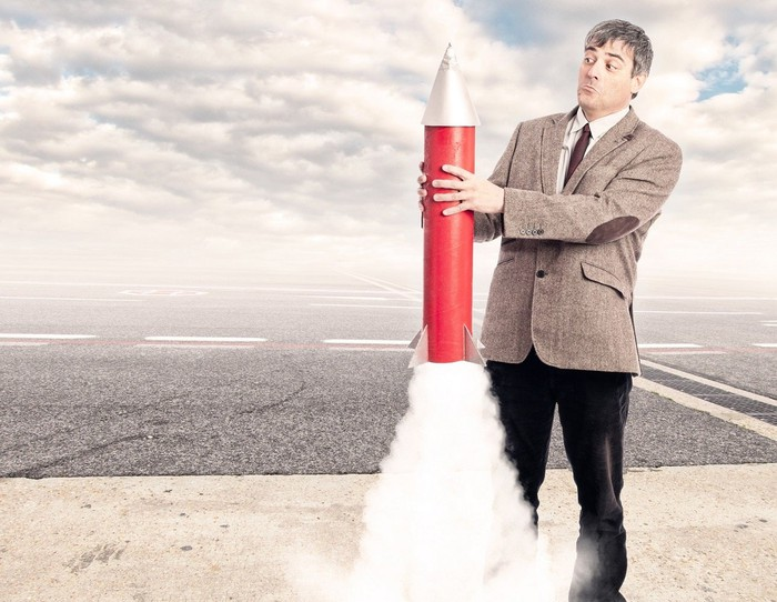 Man with surprised expression holding toy rocket that begins to launch.