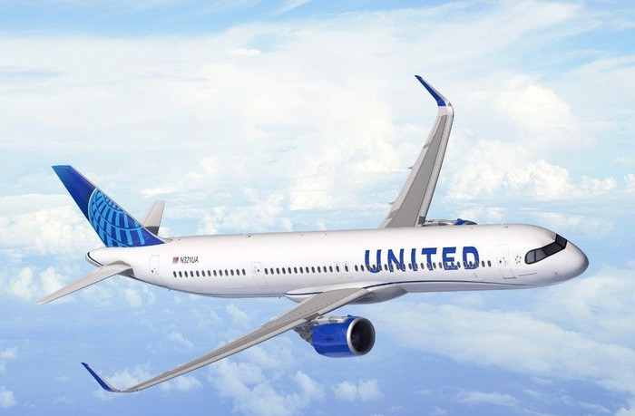 White and blue jet aircraft with United markings flying at high altitude among clouds, with views of the ground.