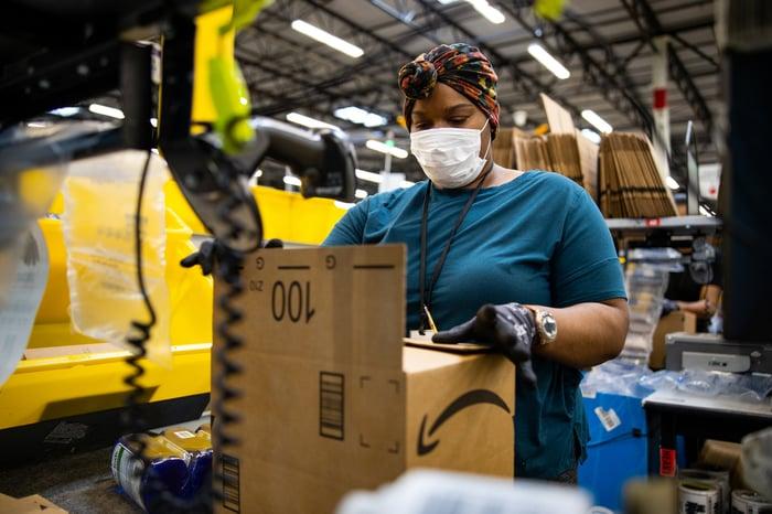 Un employé d'Amazon emballant une boîte tout en portant un masque et des gants.