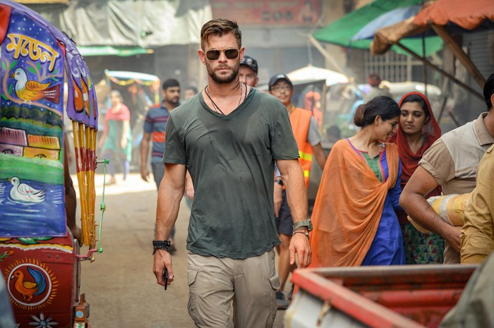 In a scene from a movie, a man wearing cargo pants, a t-shirt, and sunglasses walking through a colorful outdoor market in India.