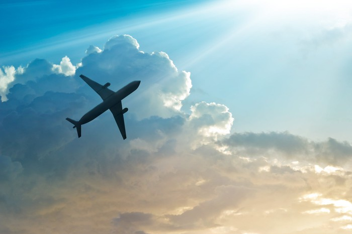 Airplane flying high against a background of clouds and sunbeam