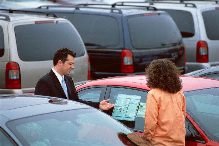Two people looking at car in sale lot