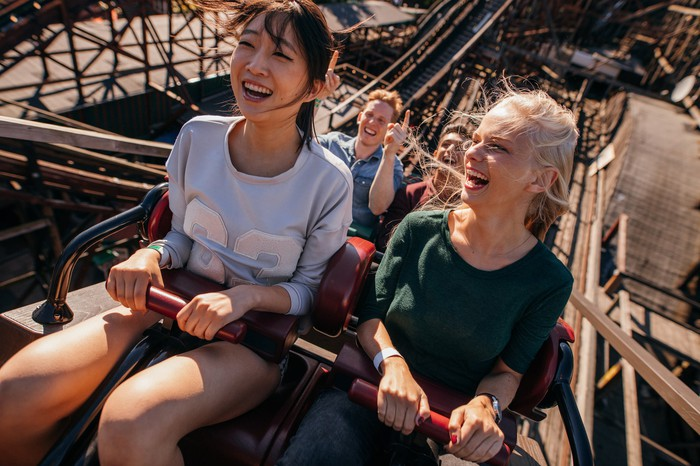 People are smiling while riding a roller coaster.