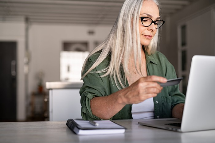 A woman looking at credit card while typing on laptop.