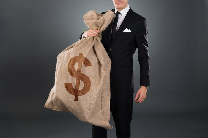 Man in a business suit carrying a large burlap sack with a dollar sign.