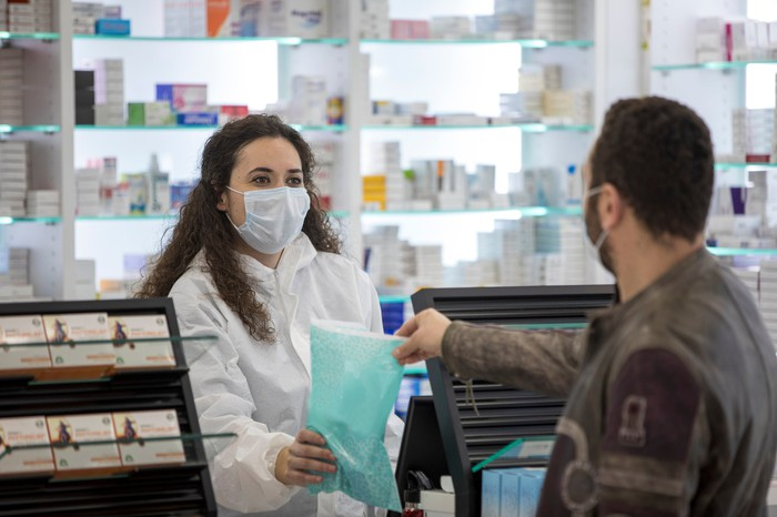 Pharmacist wearing a surgical mask while handing bag to customer.
