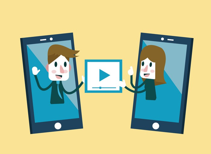 Man and woman sharing video clips via their smartphones.