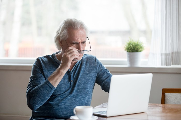 A concerned-looking senior man holding his glasses studies his laptop screen.
