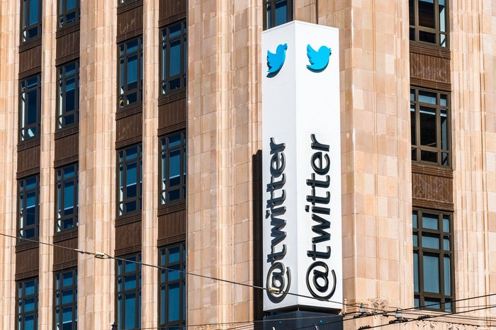 """White column with Twitter bird logo and """"@twitter"""" next to a red-brown office building."""