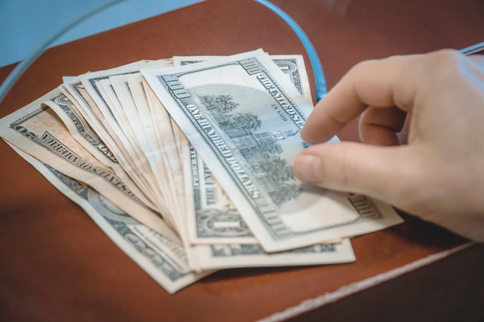 Money being passed through a bank teller window.