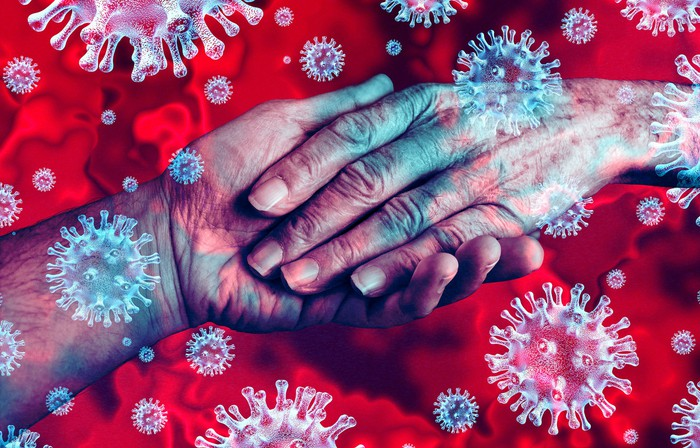 Coronaviruses imposed over a pair of elderly hands.