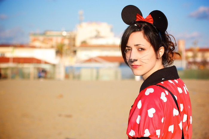 Young woman in mouse ears and makeup approaching a theme park