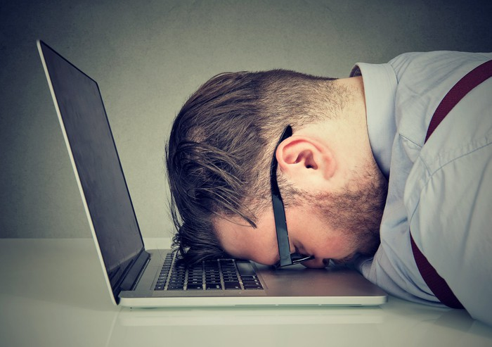 A man resting his head on the keyboard of his laptop.