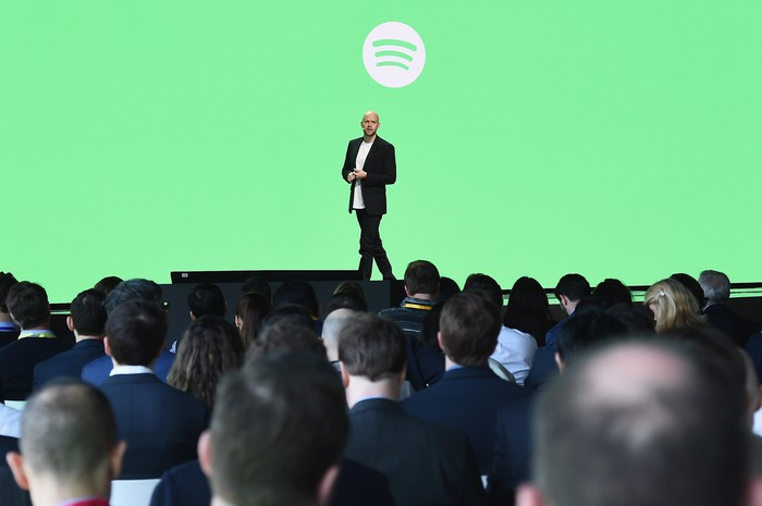 Daniel Ek on stage in front of Spotify logo with an audience watching him