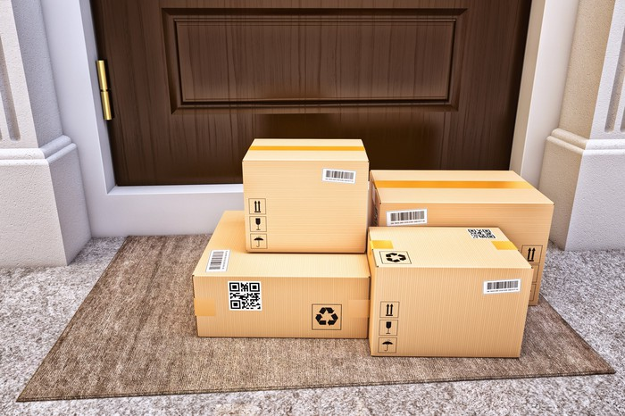 Several shipped boxes sitting in front of a door.