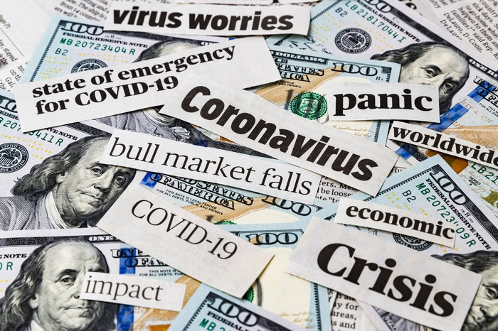 Negative phrases on small pieces of paper, like panic, COVID-19, virus worries, and impact, on top of paper money