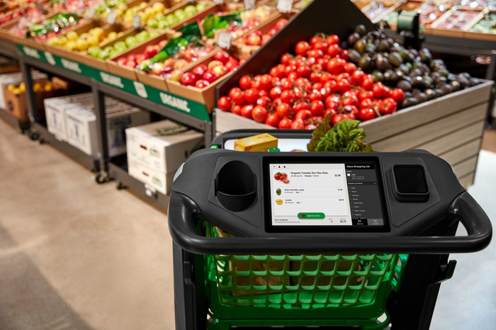 Shopping cart with Alexa integration at a Whole Foods, with produce displayed in the background