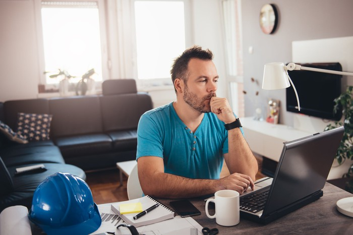 Man at laptop resting fist on chin