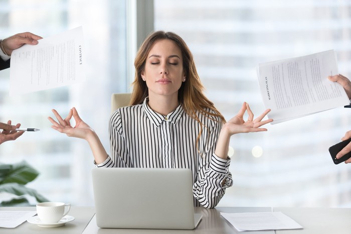 A young business woman closes eyes and touches index fingers to thumbs in meditation as hands come at her from all sides with papers and work stuff.
