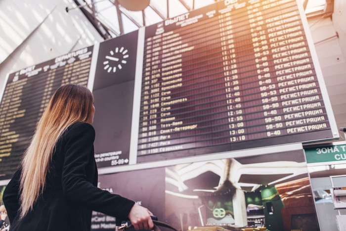 Frequent flyer looking at flight schedule board
