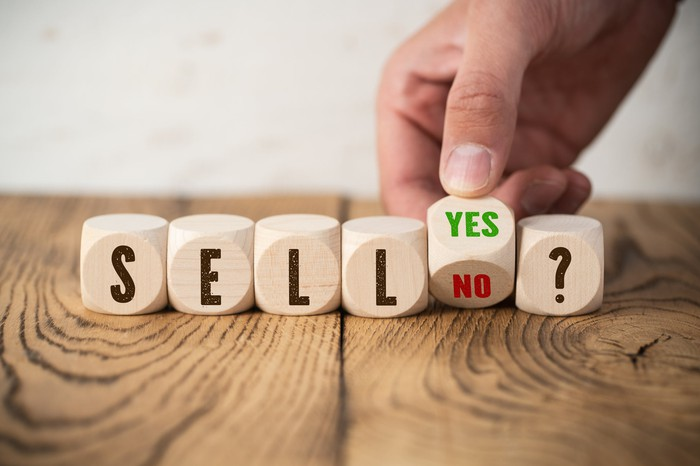 """An investor's hand turns a block marked """"yes"""" on one side and """"no"""" on the other next to blocks spelling out """"sell?"""""""