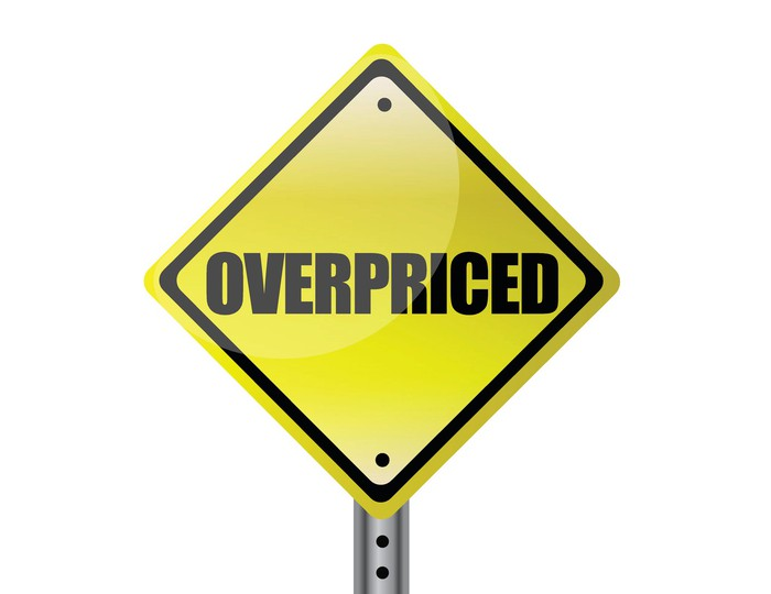 """A yellow road sign with the word """"overpriced"""" on it"""
