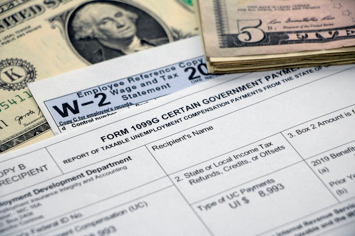 A 1099G unemployment benefits tax form and W2 next to cash.