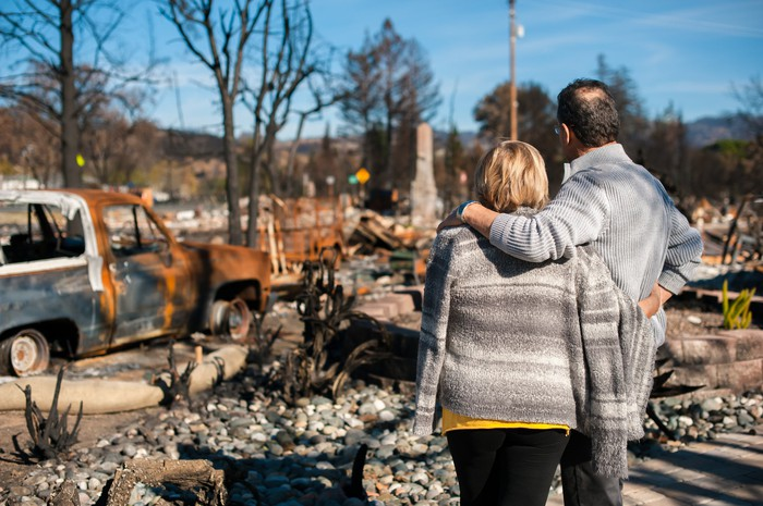 Homeowners looking at property site of a home completely destroyed by wildfire