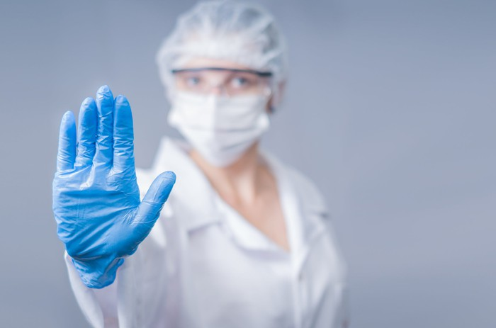 Healthcare worker in PPE holding out a gloved hand, as if to say stop.