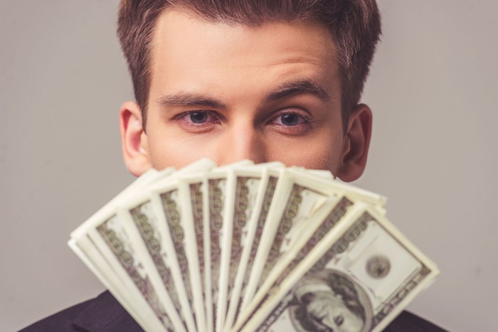 Young man holding hundred dollar bills in front of his face.