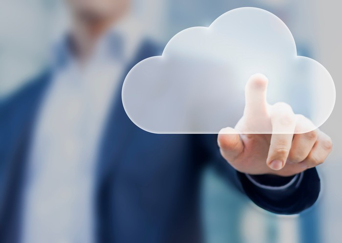 A man in business attire touching a virtual cloud icon.
