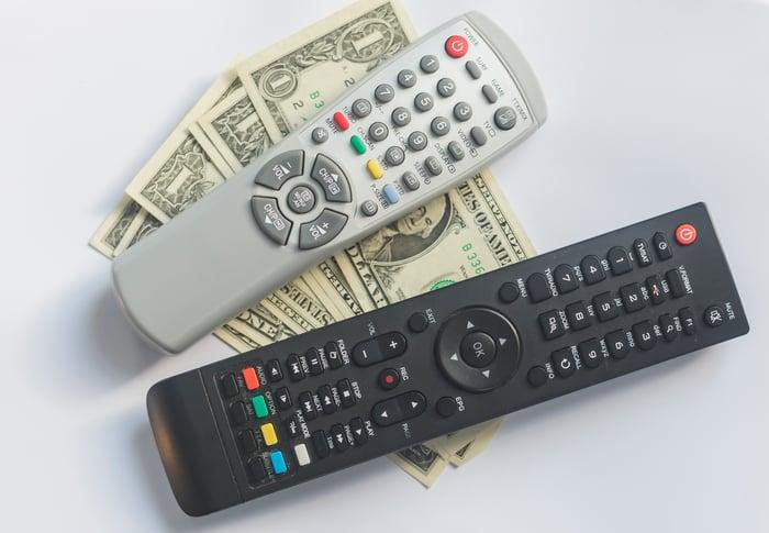 A couple of remote controls resting on a few dollar bills.