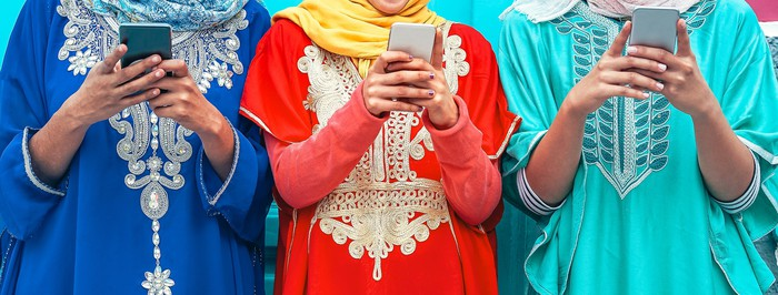Three women in traditional Indian dress using smartphones