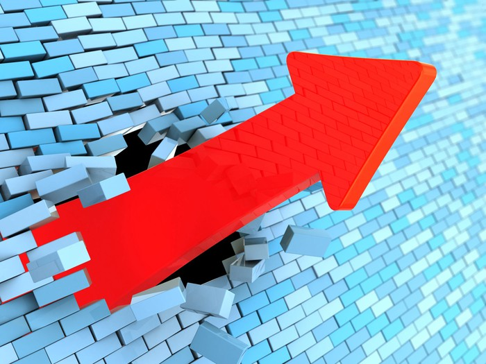 A red charting arrow smashed upward through a blue brick wall