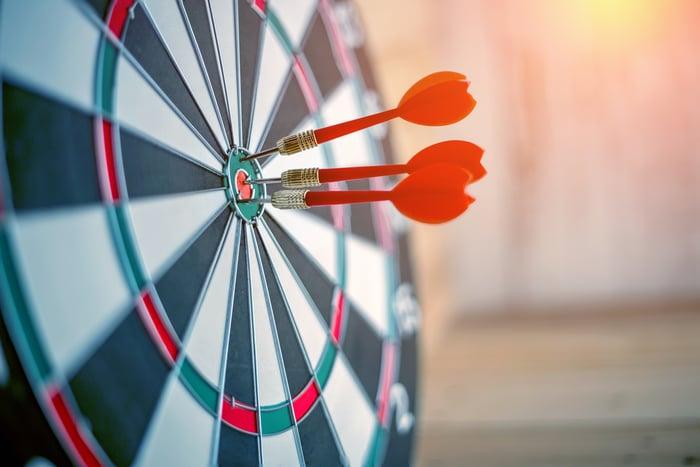 Darts in the bull's-eye of a dartboard