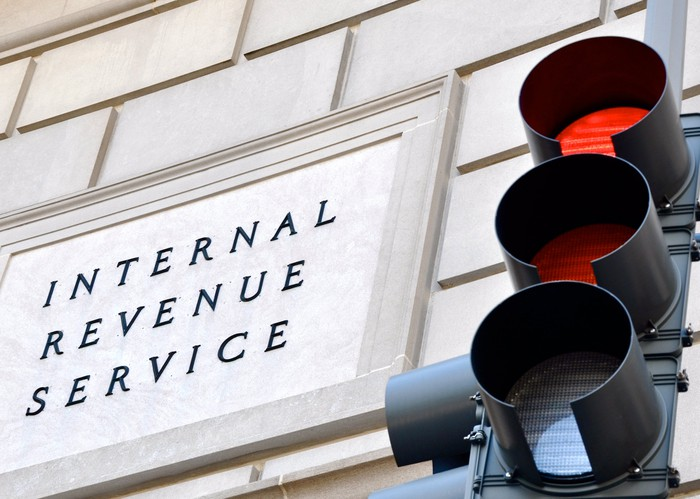 "A building facade with a sign that says ""Internal Revenue Service"" and a stoplight in front of it with one red lamp."