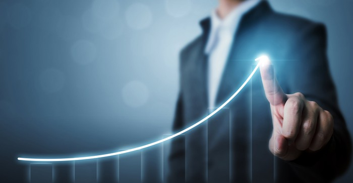 A person is pointing to an upwardly sloping chart.