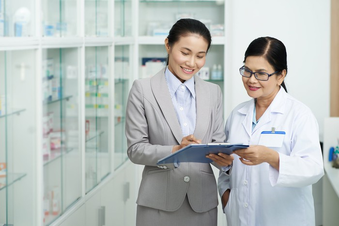 Two scientists with clipboard at a pharmacy.