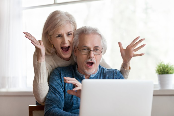 A couple looking at a laptop screen with delight and surprise.